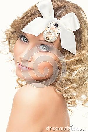 Nahaufnahmeporträt des schönen blonden mädchens mit weißem bogen