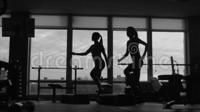 Mädchen mit Lehrer tun Eignungsübung zusammen unter Verwendung eines Schrittes in der Sportturnhalle