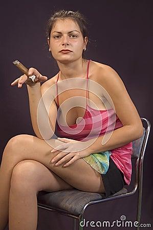 Junges mädchen das mit zigarre vor beschaffenheit des leinens sitzt