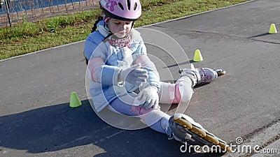 Mädchen nach dem Unfall, der auf dem Weg sitzt und massieren ihr Knie stock video