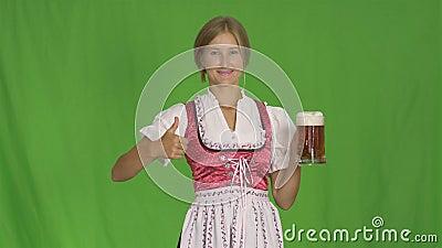 Mädchen setzt Glas Bier auf einen lokalisierten grünen Hintergrund Oktoberfest-Feier des Bayern stock footage