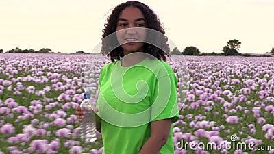 Mädchen Teenagerweibliche junge Frau, die durch das Feld rosa Mohnblumen geht, Trinkwasser aus einer Plastikflasche stock video footage