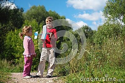 Mädchen und Junge mit Spielzeugflugzeug in den Händen