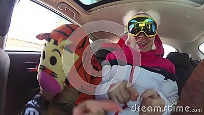 Mädchenskifahrer, der Spaß mit der Musik im Auto auf der Reise hat