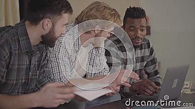 M?nner des Kaukasiers des Portr?ts zwei und eines Afroamerikaners, die zusammen zu Hause, sitzend vor Laptop stillstehen multikul stock video