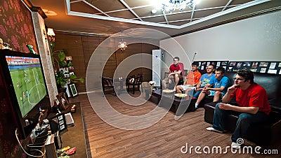 Männer, die Fußball auf Fernsehapparat überwachen