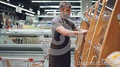 Männlicher Angestellter des großen Supermarktes nimmt frisches Brot vom Warenkorb und setzt es auf Regale in Bäckerei ein stock video footage