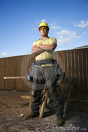 Männlicher Bauarbeiter steht mit den gefalteten Armen
