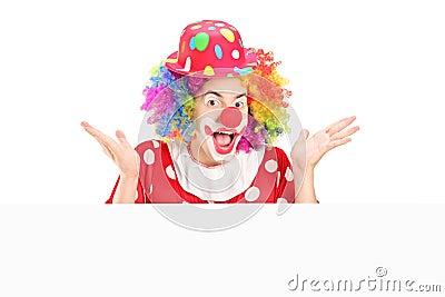 Männlicher Clown, der hinter Leerplatte gestikuliert
