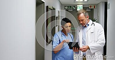 Männlicher Doktor und Kollege, die über digitaler Tablette sich bespricht stock footage