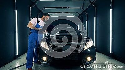Männlicher Mechaniker steht nahe einem schwarzen Automobil mit einem Laptop stock video footage
