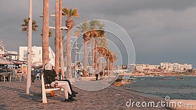 März, 16, 2019/Cyprus, touristische Promenade Paphos in Paphos, Zypern Leute, die auf Kai gehen Fußgängerweg mit Entspannungsleut stock video