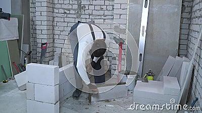 Młody caucasian budowniczego kładzenia moździerz na stronach wietrzący betonowy blok zdjęcie wideo