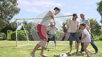 Mång- utveckling som spelar fotboll i trädgård tillsammans arkivfilmer