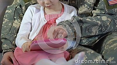 Mère dans le comprimé uniforme de jouet d'utilisation de fille d'enseignement de camouflage, loisirs de famille banque de vidéos