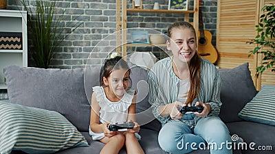 Mère et fille jouant à un jeu vidéo à la maison en s'amusant en riant ensemble clips vidéos