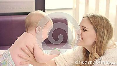Mère heureuse embrassant la chéri Bébé de caresse de jeune mère banque de vidéos