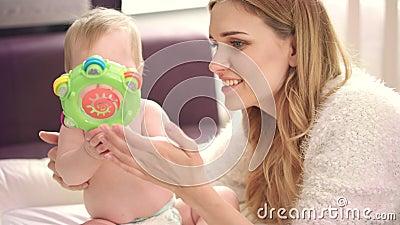 Mère jouant avec la chéri Jeu de fille de beauté avec le hochet de bébé banque de vidéos