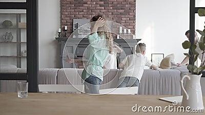 Mère occupée de portrait parlant sur une cellule tandis que tenir un ordinateur portable à disposition se tient dans la chambre d clips vidéos