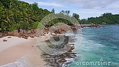 4 000 mètres d'altitude survolent une plage tropicale exotique avec des rochers, des palmiers et des vagues de l'océan sur l'île  banque de vidéos