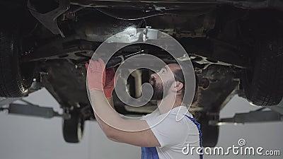 Mécanicien barbu réussi inspectant la suspension ou les freins dans la voiture avec la lampe-torche de l'automobile soulevée à la banque de vidéos