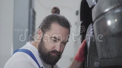 Mécanicien professionnel barbu de portrait inspectant la suspension ou les freins dans la roue de voiture de l'automobile soulevé banque de vidéos