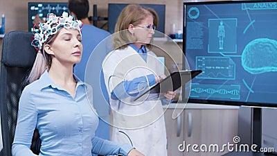Médecine féminine regardant l'écran de télévision avec activité cérébrale banque de vidéos