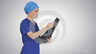 Médica feminina a olhar para o ressonância magnética do cérebro sobre o fundo gradiente vídeos de arquivo