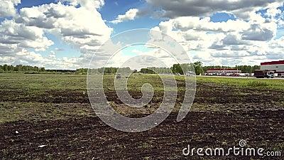 Mörk plogad jordning för flyg- sikt på fält nära modern byggnad stock video
