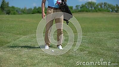 Mężczyzna golfista wkładający torbę na sprzęt sportowy na zielono, zabierający klub i gotowy do gry zbiory