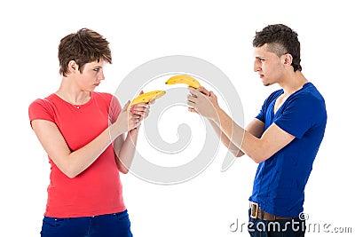 Mężczyzna i kobieta strzela each inny z bananami