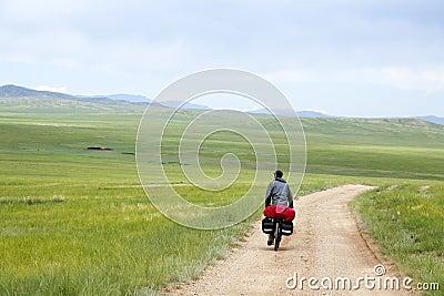 Mężczyzna jazdy rower przez Mongolskich stepów