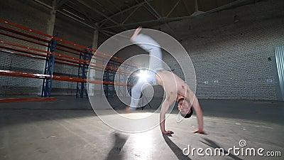 Mężczyzna robi capoeira elementom w pokoju z betonową podłogą, ścianami z cegieł i jaskrawym światłem, - cartwheel - zdjęcie wideo