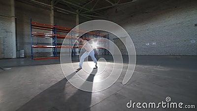 Mężczyzna robi capoeira elementom w pokoju z betonową podłogą i ścianami z cegieł - cartwheel - zbiory wideo