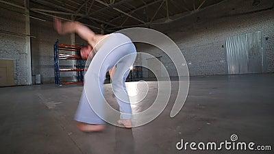 Mężczyzna robi różnym capoeira elementom w pokoju z betonową podłogą - zostający na jego ręce i robić cartwheel - zbiory wideo