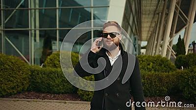 Mężczyzna rozmawiający przez telefon na zewnątrz, przystojny młody biznesmen, odbierający smartfon zdjęcie wideo