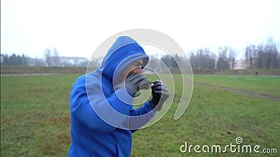 Mężczyzna sportowiec bokser facet w rękawiczkach bokserskich, ćwiczący na zewnątrz, wbijający się, mężczyzna w masce wyglądający  zdjęcie wideo