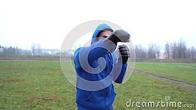 Mężczyzna sportowiec bokserski facet w rękawiczkach bokserskich trenujący na zewnątrz, robiący szaty i uderzenia, mężczyzna w oka zdjęcie wideo