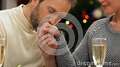 Mężczyzna tenderly całuje kobiety rękę, romantyczna data na Bożenarodzeniowej nocy, zbliżenie zbiory