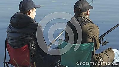 Męscy przyjaciele łowi, siedzący na falcowań krzesłach, rekreacyjna aktywność plenerowa zbiory