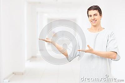 Męska cierpliwa jest ubranym szpitalna toga i gestykulować z rękami w a
