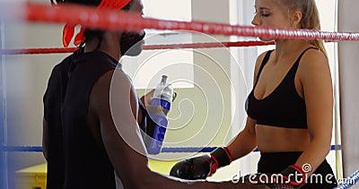 Męska trenera karmienia woda żeński bokser w bokserskim pierścionku 4k zdjęcie wideo