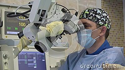 Męski chirurg wykonuje mikroskopijną operację na pacjenta ENT organach używać chirurgicznie mikroskop nowatorski zbiory