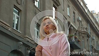 Młoda atrakcyjna blondynka w różowym płaszczu stoi na tle starej architektury zbiory