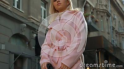 Młoda atrakcyjna blondynka w różowym płaszczu stoi na tle starej architektury zdjęcie wideo