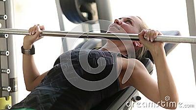 Młoda atrakcyjna dama pracująca w gym out klatka piersiowa mięśnie ćwiczy - podnoszący barbell - zbiory wideo