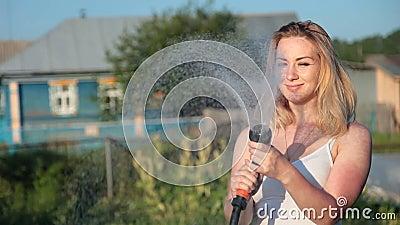 Młoda blond kobieta nawadnia ogród zbiory