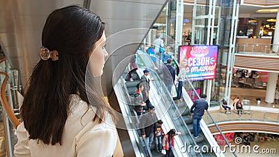 Młoda dziewczyna patrzeje od najwyższego piętra na ludziach w handlu centrum zdjęcie wideo