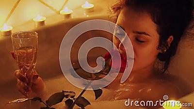 Młoda dziewczyna relaksuje mieć terapię w łazience z pianą z wzrastał w ręce i szkle wino zdjęcie wideo