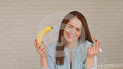 Młoda dziewczyna z typem - 1 cukrzyce z insuliną i bananem w ona w domu ręki zbiory wideo